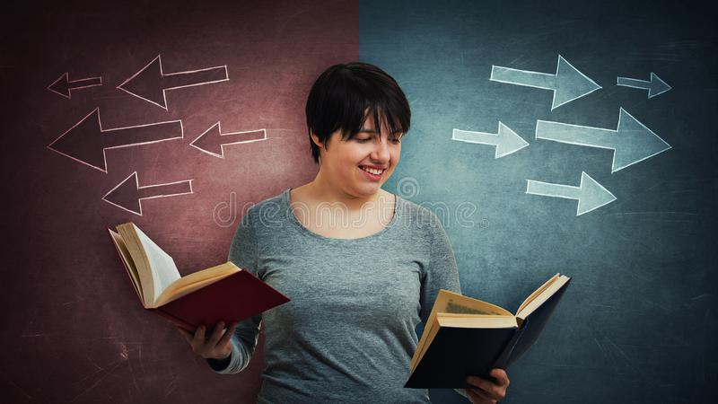 Student choosing book to read. Woman student or teacher holding two books, red and blue, choosing which to read, as arrows on the blackboard going to different stock photography
