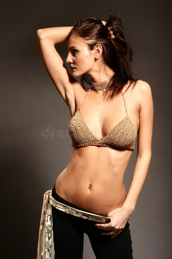 Woman in studio in golden bikini top stock images