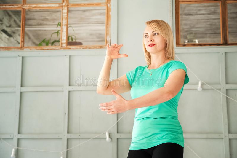 A woman in the studio practicing Chinese martial art Tai Chi close-up and copy space.  royalty free stock images