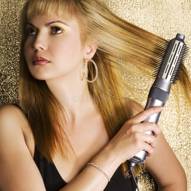 Woman styling her hair stock photography