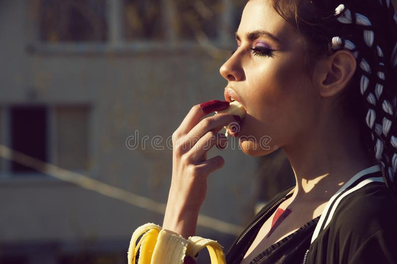 Woman with stylish makeup, long braids eating organic banana. Woman with stylish makeup, long braids, brunette hair, eating organic banana on sunny day outdoors stock image