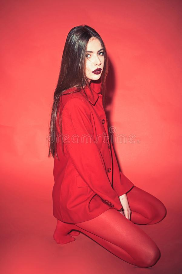 Woman with stylish makeup and long hair posing in total red outfit. Fashion concept. Girl on calm face in red formal. Jacket and tights, red background. Lady royalty free stock photo