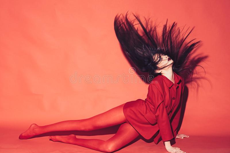 Woman with stylish makeup and long hair posing in total red outfit. Fashion concept. Girl on mysterious face in red. Formal jacket and tights, red background stock photos