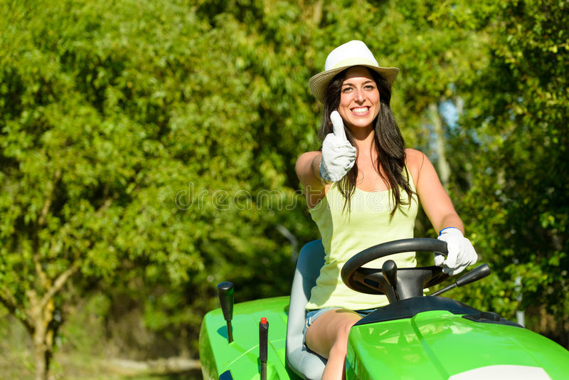 Woman success in field garden job. Successful and happy female gardener riding garden tractor doing approval gesture with thumbs up. Woman riding lawn mower stock photography