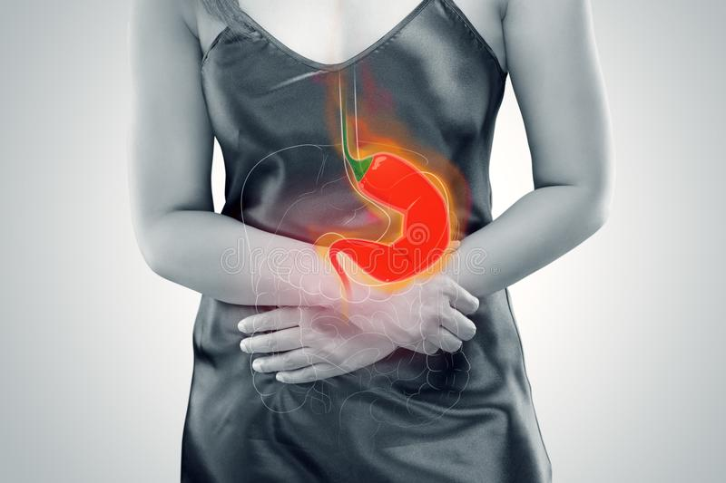 Acid Reflux Or Heartburn. Woman Suffering From Acid Reflux Or Heartburn - Against gray background royalty free stock image