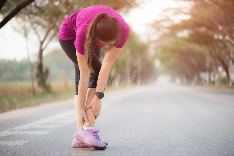 Woman suffering from an ankle injury while exercising. Running sport injury concept royalty free stock photos