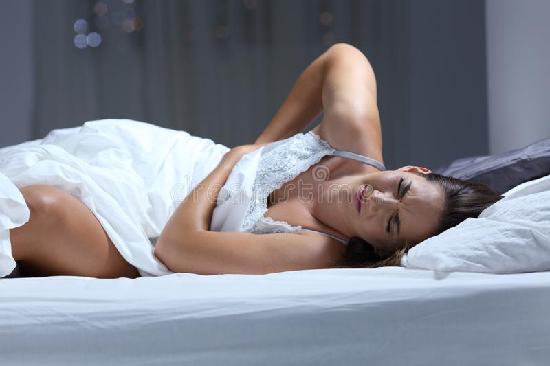 Woman suffering back ache on a bad mattress royalty free stock image