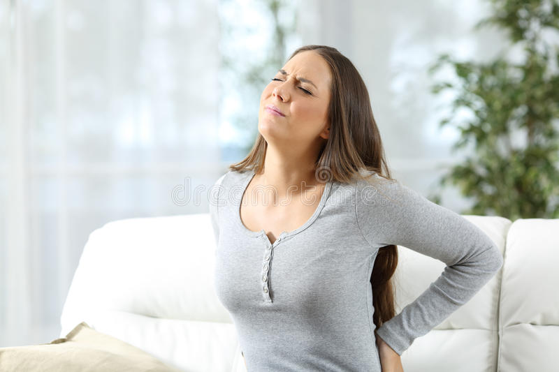 Woman suffering back ache stock images