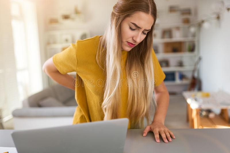 Woman suffering backache while using laptop stock images