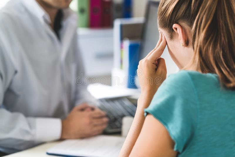 Woman suffering from bad headache or migraine. Appointment with doctor in office room. royalty free stock photography