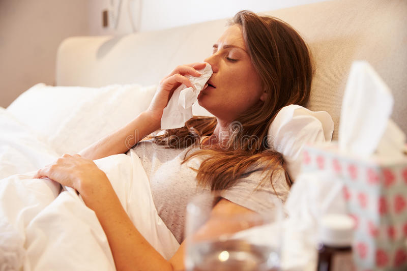 Woman Suffering From Cold Lying In Bed With Tissue stock photography