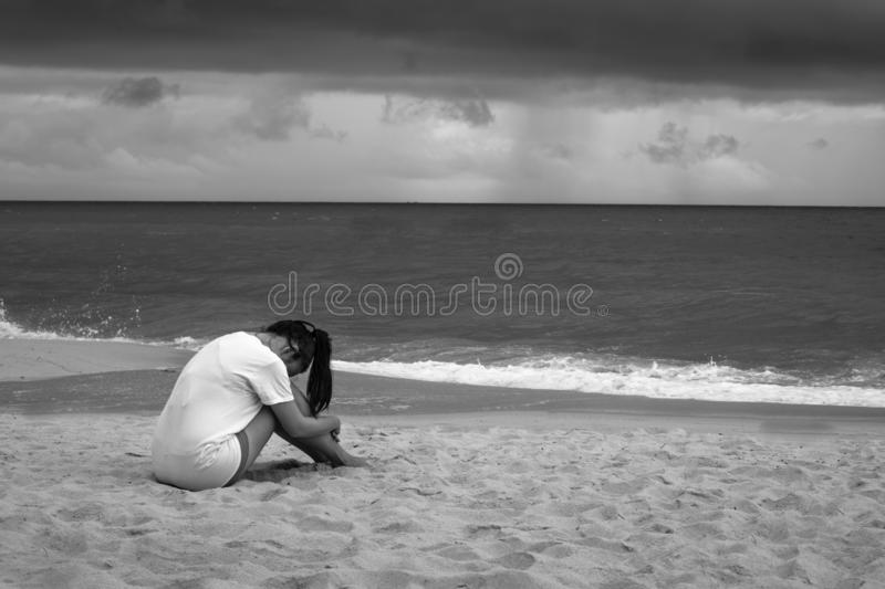 Young sad woman sitting on the beach crying in the rain. Black and white stock images