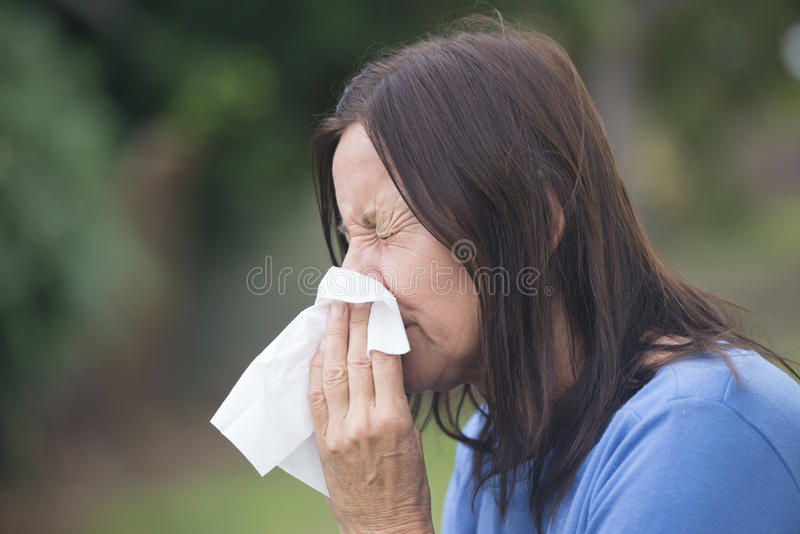 Woman suffering flu sneezing in tissue stock photos