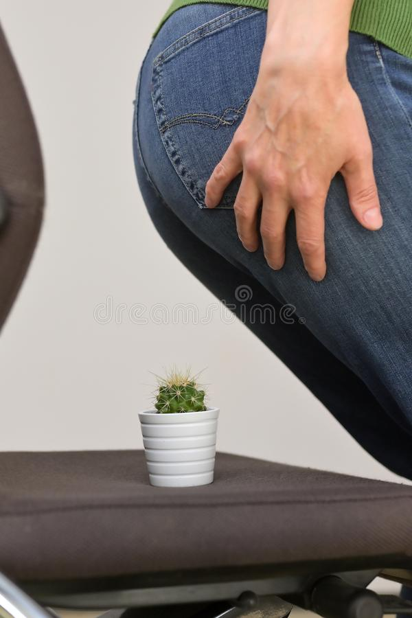 Woman Suffering From Hemorrhoids And Thorny Cactus royalty free stock images