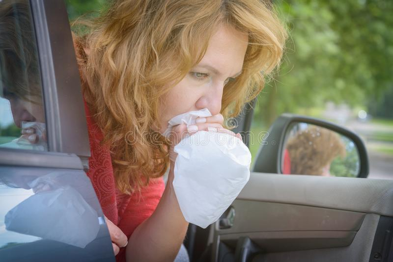 Woman suffering from motion sickness. In a car and holding sick bag royalty free stock photography