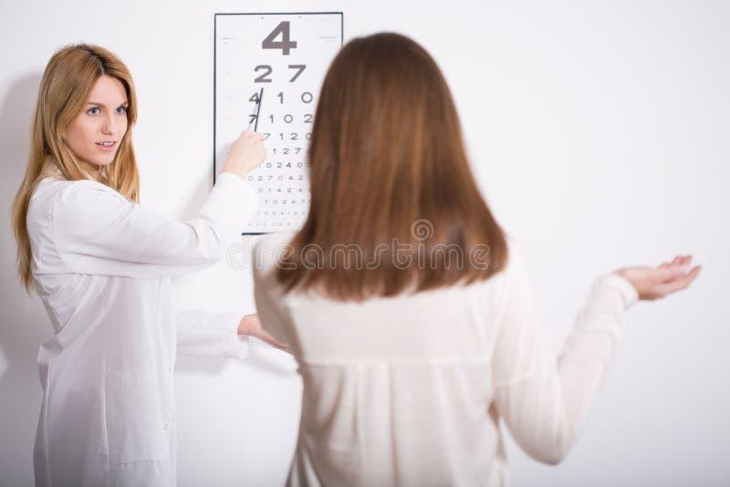 Woman suffering for myopia. During eye exam stock image