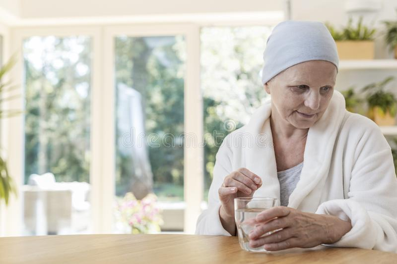 Woman suffering from ovarian cancer wearing bathrobe and headscarf taking pills at home. stock image