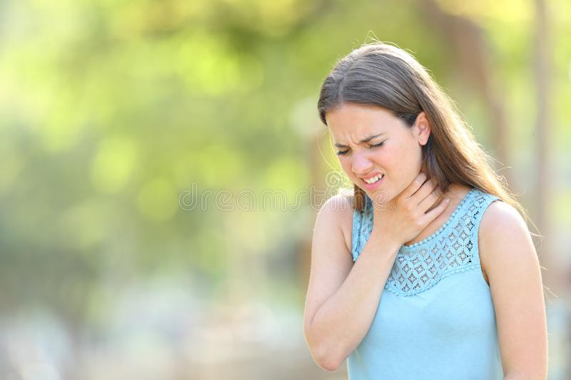 Woman suffering sore throat in a park. Standing outdoors in a park stock image