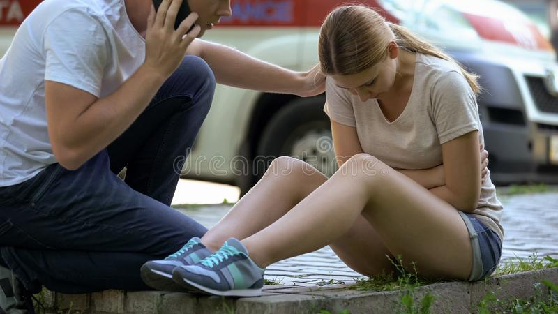 Woman suffering stomach pain, not indifferent man calling ambulance, first aid. Woman suffering stomach pain, not indifferent men calling ambulance, first aid royalty free stock images