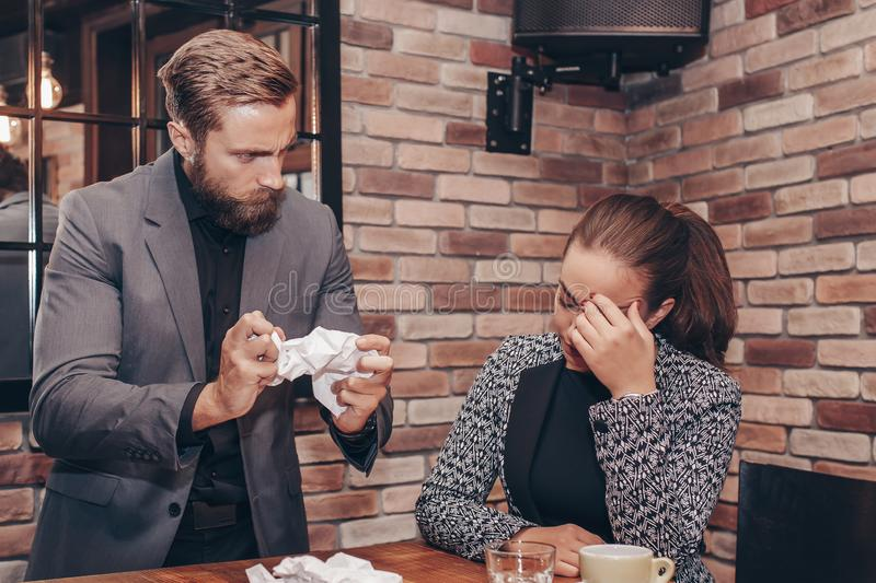 Woman suffering from stress because of angry male colleague royalty free stock image