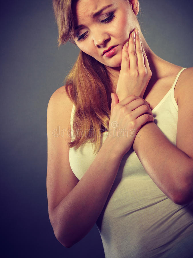 Woman suffering from tooth pain. Dental care and toothache. Young woman achy girl suffering from terrible tooth pain, touching pressing her cheek by hand palm stock images