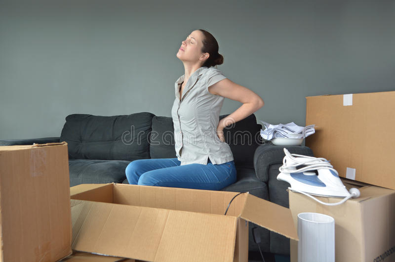 Woman suffers from back pain due to unpacking boxes stock photo