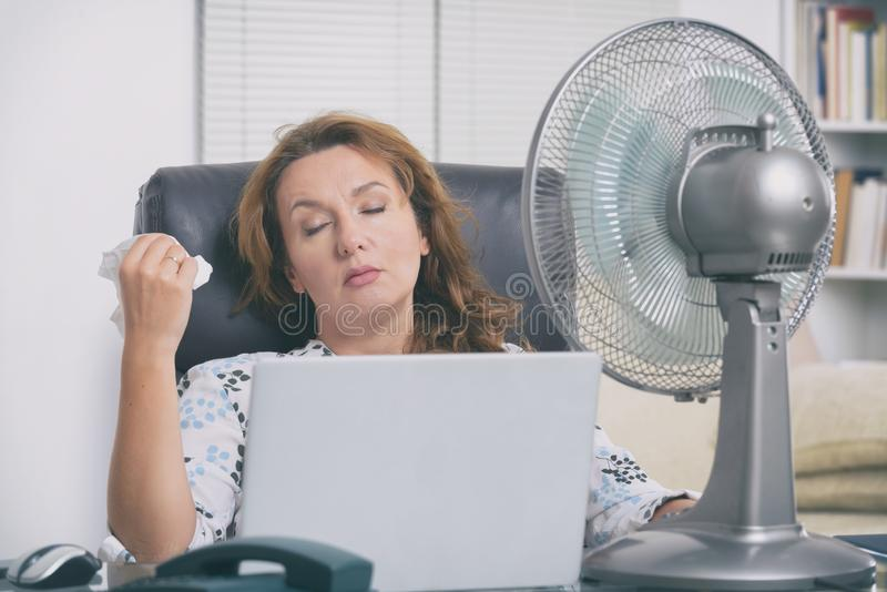 Woman suffers from heat in the office or at home royalty free stock photos