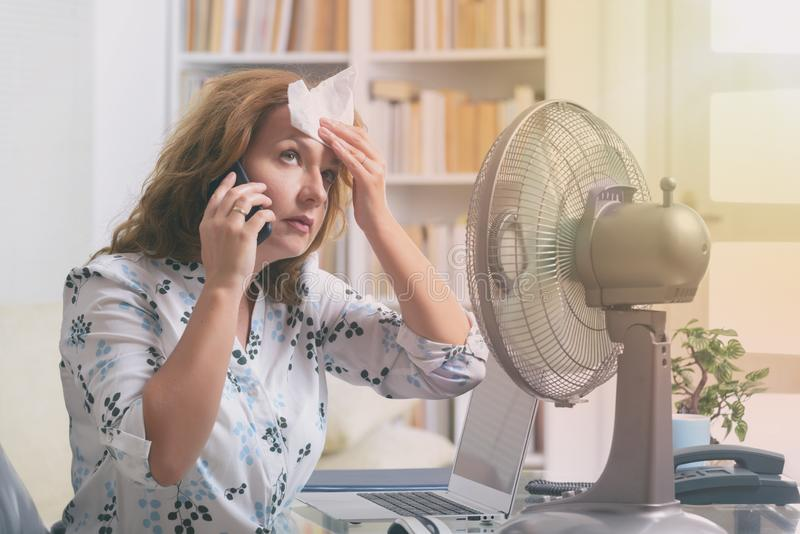 Woman suffers from heat in the office or at home stock images