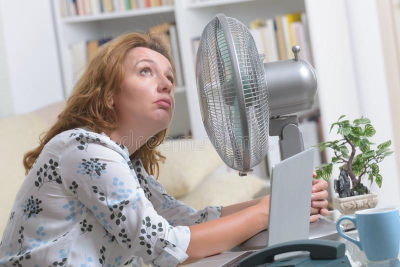 Woman suffers from heat in the office or at home stock image