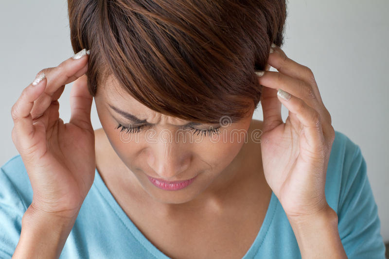 Woman suffers from pain, headache, sickness, migraine, stress. Insomnia, hangover in casual dress, two hands holding head royalty free stock image