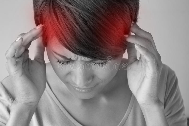 Woman suffers from pain, headache, sickness, migraine, stress. Insomnia, hangover in casual dress, two hands holding head stock image