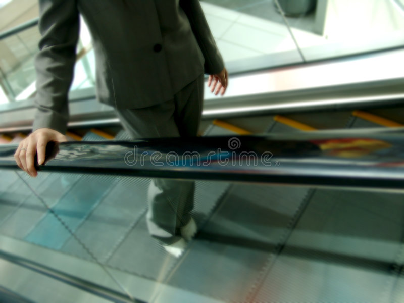 Woman in Suit Going Up the Escalator. Woman wearing a business suit going upwards on the escalator royalty free stock photo