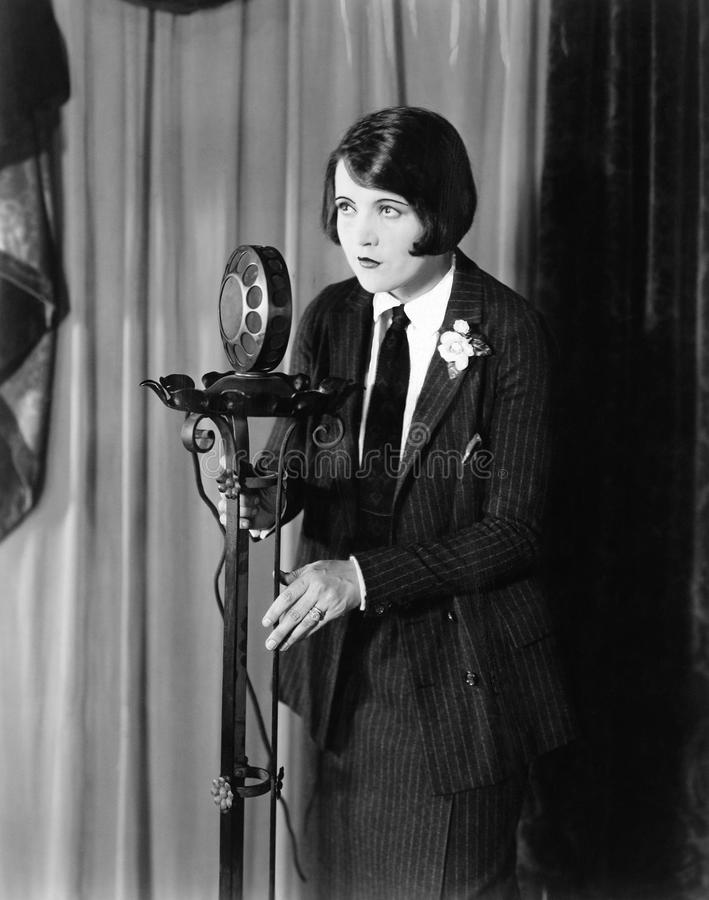 Woman in suit at microphone. (All persons depicted are no longer living and no estate exists. Supplier grants that there will be no model release issues royalty free stock photo