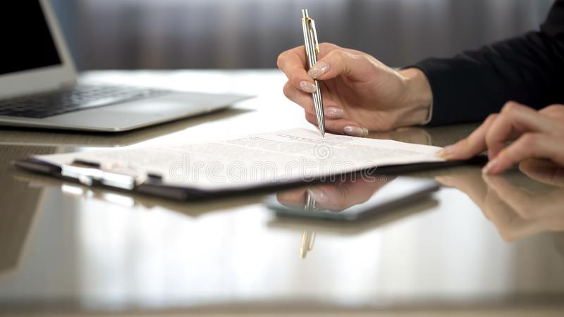 Woman in suit reading terms and conditions of agreement, signing contract. Stock photo royalty free stock photos