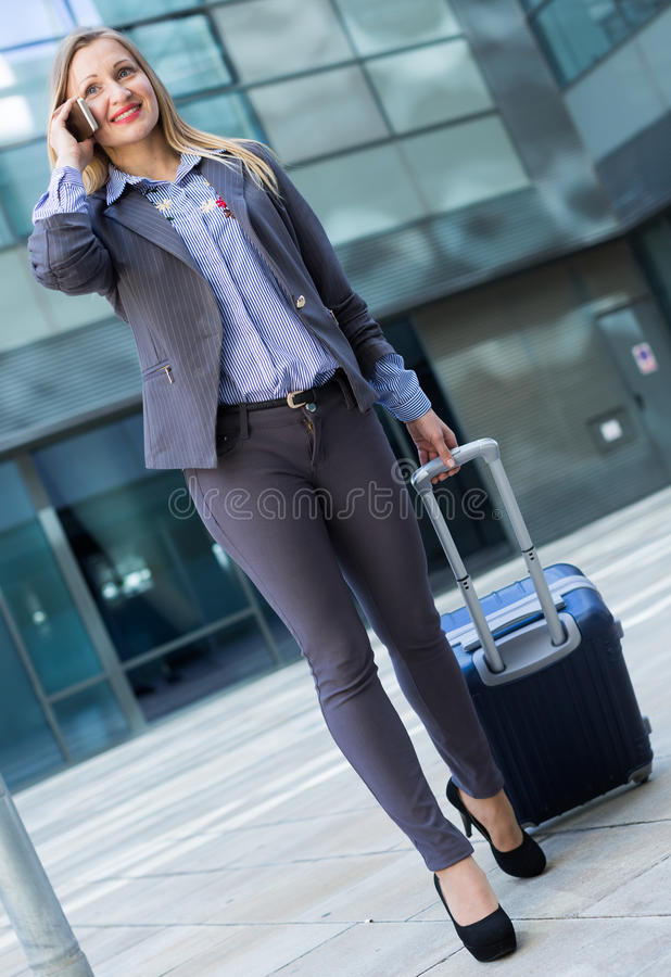 Woman in suit standing with baggage and talking phone royalty free stock images