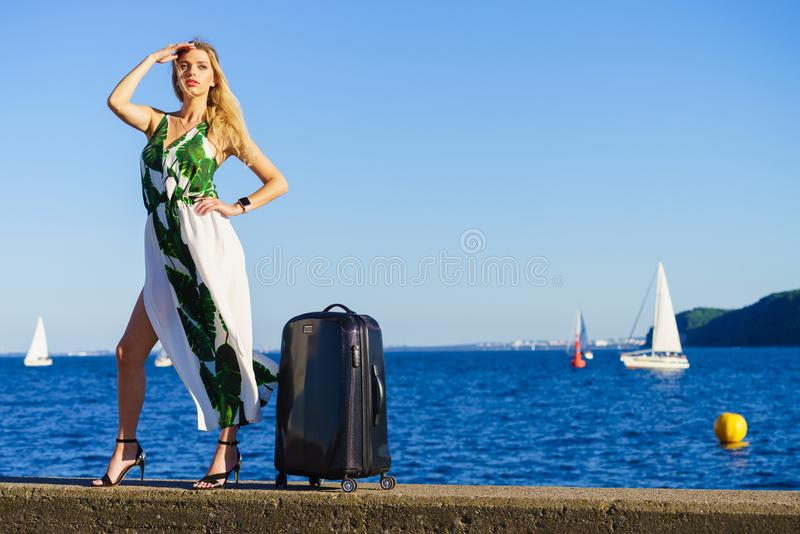 Woman with suitcase against yachts on sea royalty free stock image