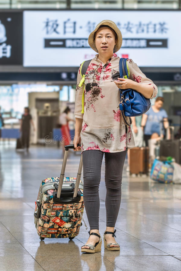 Woman with suitcase at Beijing Railway Station South, China stock photography