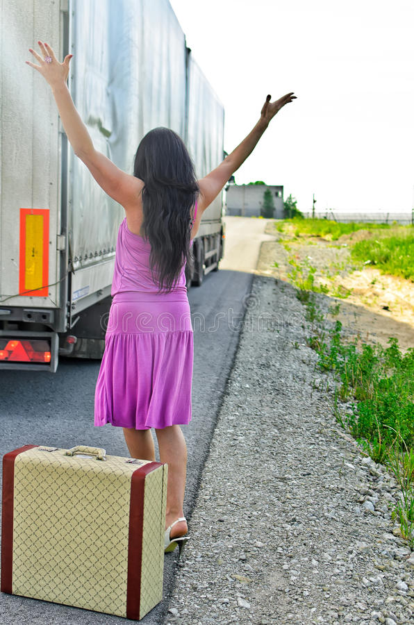 Woman with suitcase hitchhiking