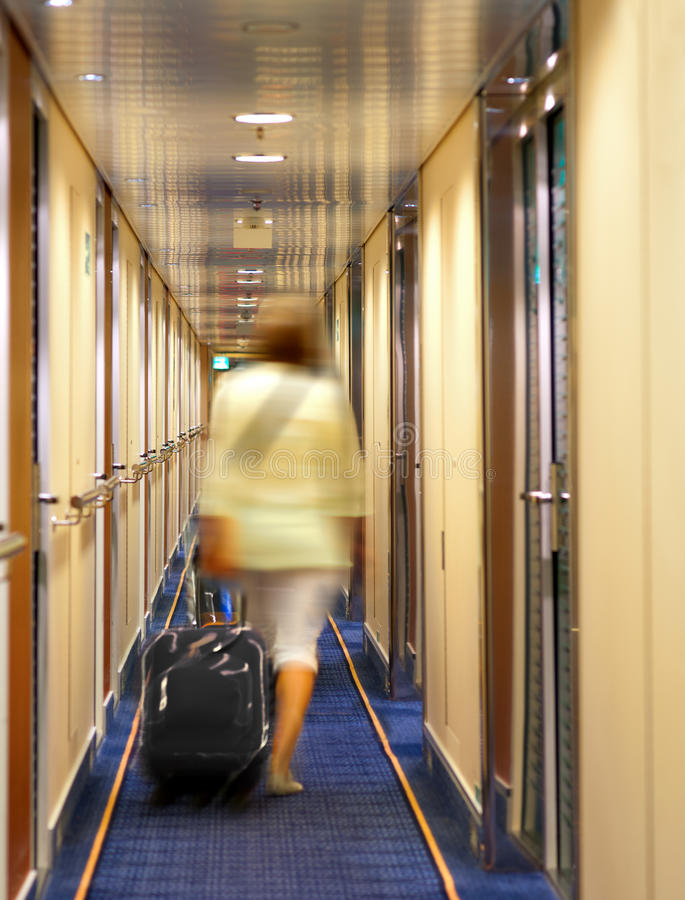 Woman with suitcase in hotel stock photography
