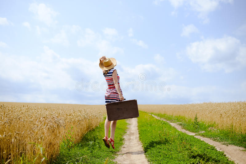 Woman with suitcase jumping on road between field royalty free stock photos