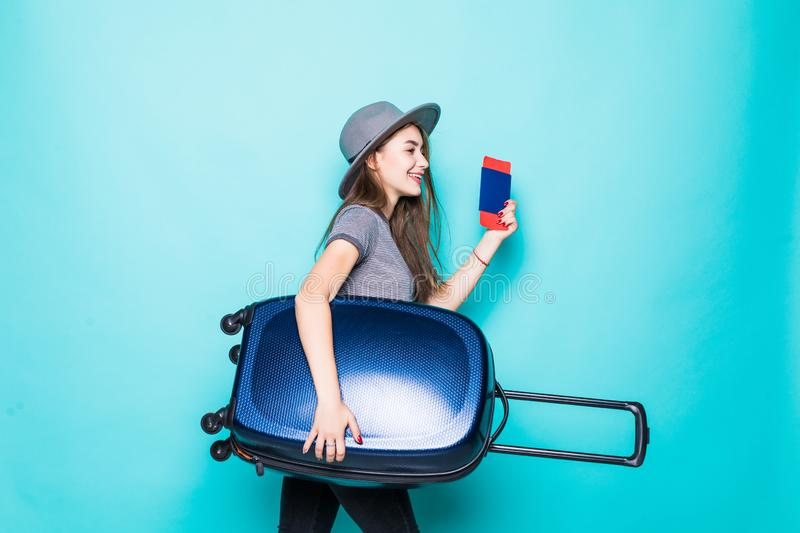 Woman with suitcase and passport running on blue color background. Woman with suitcase and passport running on color background royalty free stock photos