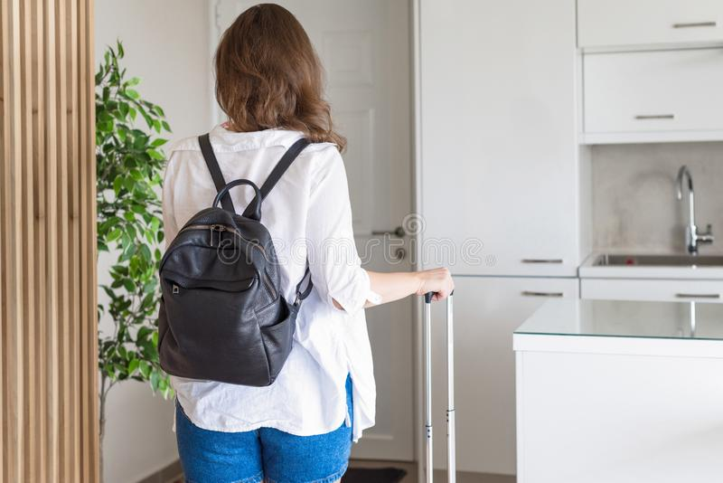 Woman with suitcase in shirt and shorts going to the door and waiting a taxi. ready to trip. Individual traveler. royalty free stock image