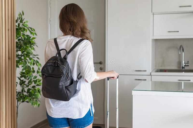 Woman with suitcase in shirt and shorts going to the door and waiting a taxi. ready to trip. Individual traveler. Woman with suitcase in shirt and shorts going royalty free stock image