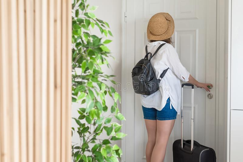 Woman with suitcase and straw hat in shirt and shorts going to the door and waiting a taxi. ready to trip. Individual traveler.  stock photos