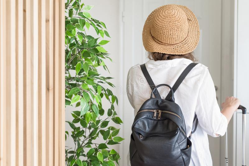 Woman with suitcase and straw hat in shirt and shorts going to the door and waiting a taxi. ready to trip. Individual traveler.  royalty free stock photography