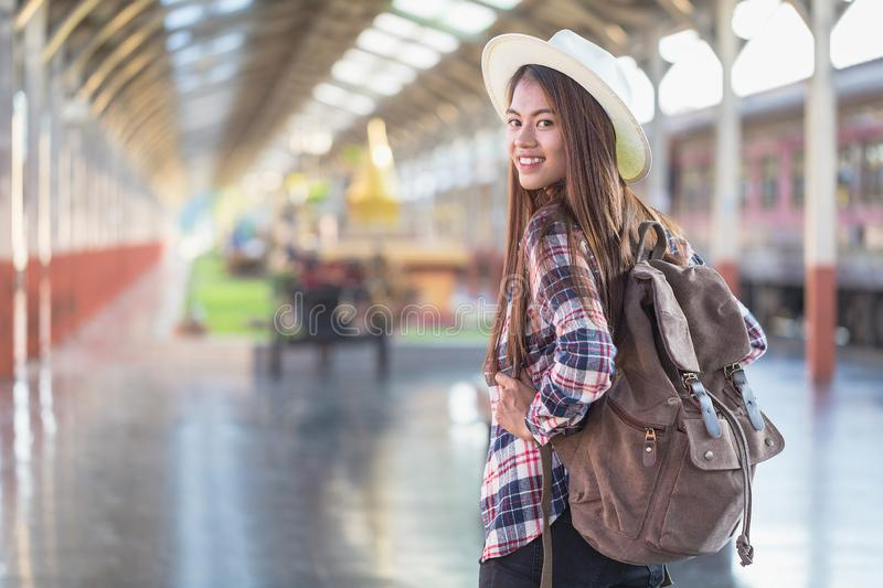 Woman with suitcase waiting for her train on platform of railway station, summer travel royalty free stock photos