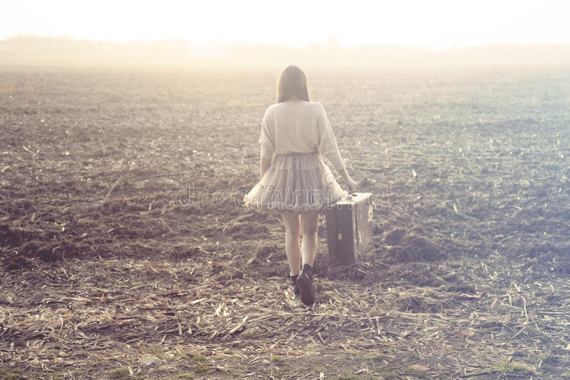 Woman with suitcase walking toward infinity in a desert place stock photography