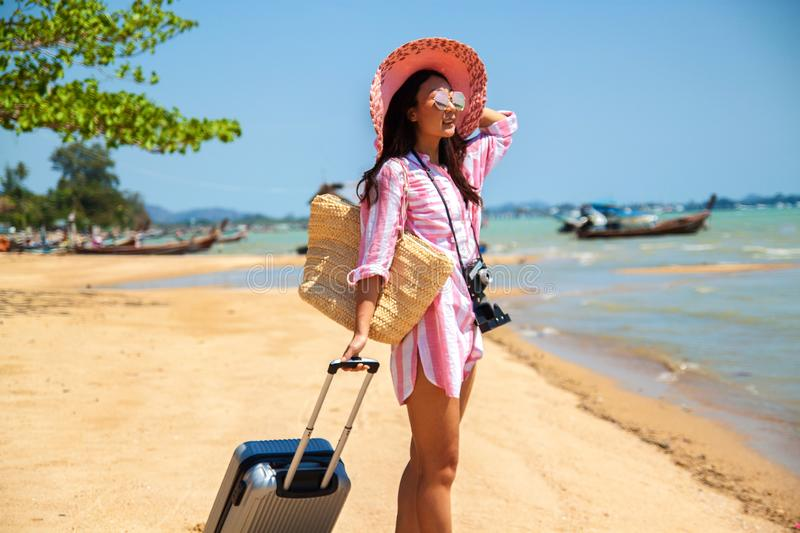 Woman with suitcase on the wonderful sea background, concept of time to travel. Beautiful young asian woman with a hat and camera standing with suitcase on the stock photos