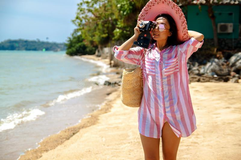 Woman with suitcase on the wonderful sea background, concept of time to travel. Beautiful young asian woman with a hat and camera standing with suitcase on the stock images