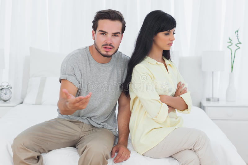 Woman sulking and her boyfriend doesnt know what to do stock photo